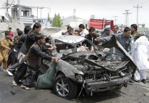 Photo by: Ahmad Jamshid ** FILE ** Afghans push a damaged car from the scene of a militant attack by a suicide car bomber and Taliban militants disguised in burqas in Kabul, Afghanistan, on Wednesday, May 2, 2012. (AP Photo/Ahmad Jamshid)
