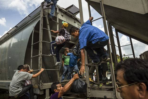 """Meridith Kohut/The New York Times  Migrants ran and climbed aboard a northbound freight train known as """"The Beast"""" as it passed through Tenosique, Mexico, earlier this month."""