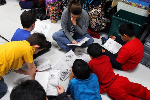 Photo by Jennifer Whitney  A reading assistant reads on the classroom floor with a small group of fourth graders at Wanke Elementary School in San Antonio on March 9, 2012.
