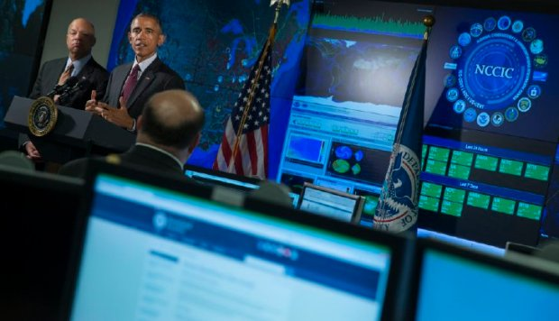 Homeland Security Secretary Jeh Johnson listens at left as President Barack Obama speaks at the National Cybersecurity and Communications Integration Center in Arlington, Va. One of the federal government's special incompetencies is protecting sensitive data. (AP Photo/Evan Vucci)